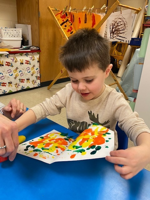 child opening art project of folded paper with paint squished inside