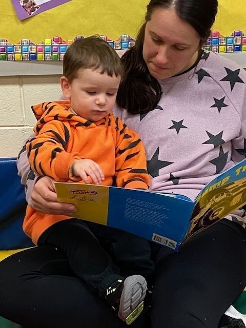 mother reading child a dump truck book