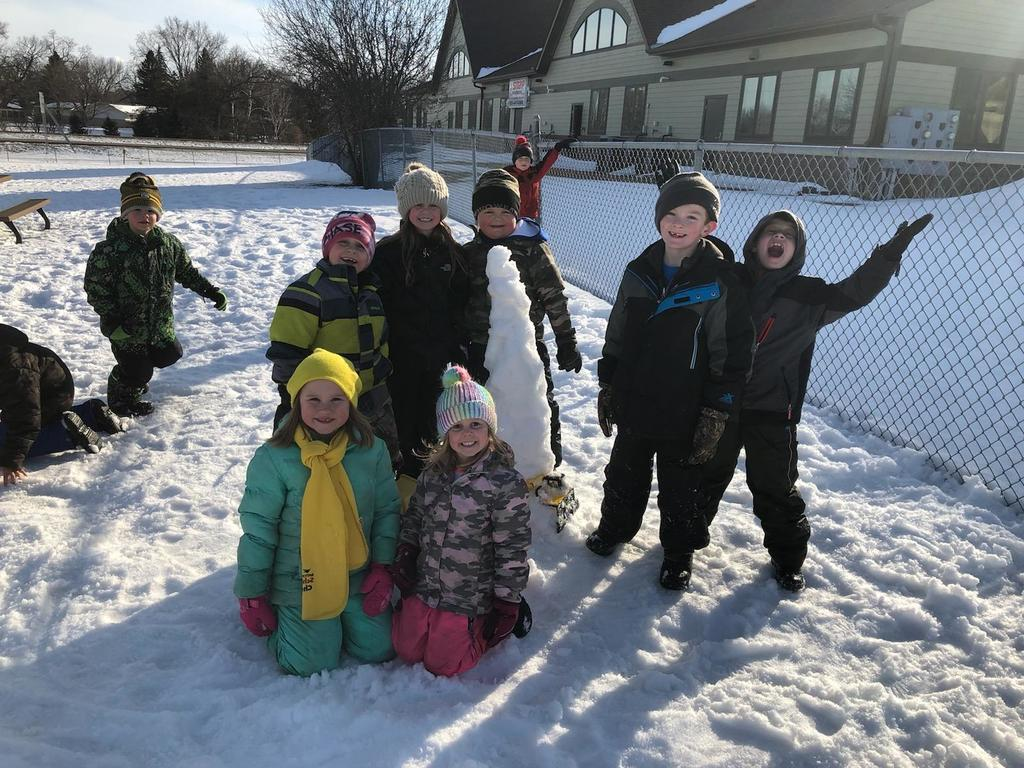 Kids outside around a tower of snow