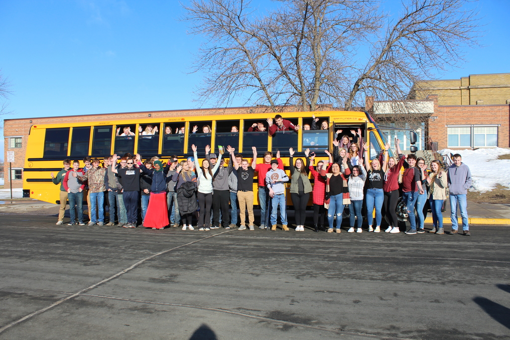 senior students arms up in front of bus